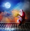 Santa Claus sitting on the roof holdig a gift in his hands Royalty Free Stock Photo