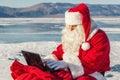 Santa Claus sitting on snow, looking at laptop news Royalty Free Stock Photo