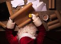 Santa Claus sitting at the table in his room and reading Christmas letter or wish list Royalty Free Stock Photo