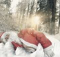 Santa claus sleeping on snow in front of gifts at forest environ Royalty Free Stock Photo