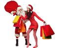 Santa claus with smiling woman his sack full of presents and women in red dress and helper hat shopping bags Royalty Free Stock Image