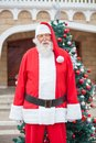 Santa claus standing against christmas tree Stockfotografie