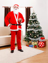 Santa Claus standing in front of Christmas Tree Stock Photography