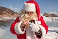 Santa claus standing outdoors at ice that calls to whom by phone Royalty Free Stock Image