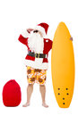 Santa Claus standing with surf board Royalty Free Stock Photo