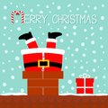 Santa Claus stuck in the chimney on the roof. Gift box. Red Royalty Free Stock Photo