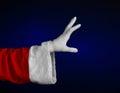 Santa claus theme santa s hand showing gesture on a dark blue background studio Royalty Free Stock Photos
