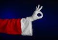 Santa claus theme santa s hand showing gesture on a dark blue background studio Stock Photos