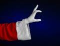 Santa claus theme santa s hand showing gesture on a dark blue background studio Stock Photography