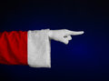 Santa claus theme santa s hand showing gesture on a dark blue background studio Stock Photo
