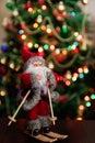 Santa Claus toy brings Christmas tree at blue snowy night bokeh Royalty Free Stock Photo