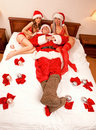 Santa Claus with two sexy girls Royalty Free Stock Photography