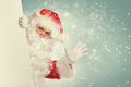 Santa claus waving hello from behind white blank banner Stock Photography