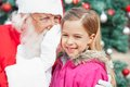 Santa claus whispering in happy girls ohr Stockbild