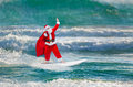 Santa Claus windsurfer with gifts sack surfing at ocean waves Royalty Free Stock Photo