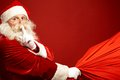 Santa coming portrait of claus with huge red sack keeping forefinger by his mouth and looking at camera Stock Image
