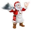 Santa cook christmas dinner concept cartoon claus cooking food with in an apron holding a silver platter and doing a perfect Stock Photo