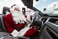 Santa driving convertible at airport terminal portrait of with pilot and airhostess standing in background Royalty Free Stock Image
