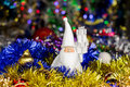 Santa figure with Christmas balls, tinsel on blurred lights background Royalty Free Stock Photo