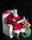 Santa figurine sitting and writing on black background Royalty Free Stock Photography
