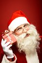Santa with giftbox photo of claus holding red by his ear Royalty Free Stock Photo