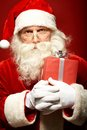 Santa with giftbox photo of serious claus red looking at camera Royalty Free Stock Images