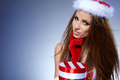 Santa girl on blue background in claus costume Stock Images