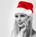 Santa girl with cell phone blonde happy young woman with christ christmas hat calling by mobile portrait black and white Royalty Free Stock Photography