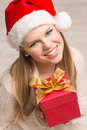 Santa girl with christmas gift portrait of happy smiling lady wearing warm knitted clothes young attractive caucasian female model Royalty Free Stock Images