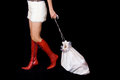 Santa girl dragging bag with gifts in red boots and fur skirt is Stock Image