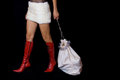 Santa girl dragging bag with gifts in red boots and fur skirt is Royalty Free Stock Image