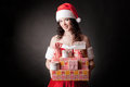 Santa girl is holding Christmas gifts. Royalty Free Stock Photos