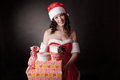 Santa girl is holding Christmas gifts. Stock Images