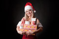 Santa girl is holding Christmas gifts. Stock Photo
