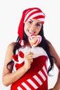 Santa girl holding a lollipop. Stock Photos