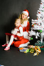 Santa girl playing with little girl Stock Image