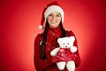 Santa girl portrait of happy in cap holding white teddy bear and looking at camera Royalty Free Stock Images