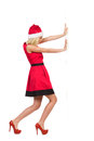 Santa girl pushing the wall christmas in red dress s hat and high heels a full length studio shot isolated on white Stock Photos