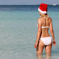 Santa Girl on Tropical Beach. Beautiful blonde young woman Royalty Free Stock Photo