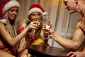 Santa girls clinking glasses of champagne with man Stock Photography