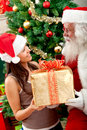 Santa giving a gift to a woman Royalty Free Stock Images