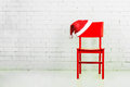 Santa hat on a chair against brick wall christmas concept Royalty Free Stock Images