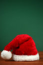 Santa hat with copy space vermelha no fundo verde e de madeira Fotografia de Stock Royalty Free