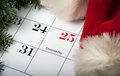 Santa hat laying on a christmas calendar next to december th with evergreens Stock Photo
