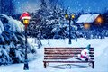 Santa hat and New Year`s soft toy on a bench in the winter forest against the background of a village house and lantern. Christma Royalty Free Stock Photo