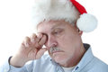 Santa hat on tired senior man older rubs his eye while wearing Royalty Free Stock Photo