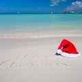 Santa Hat on white sandy beach and Merry Christmas Royalty Free Stock Photo