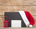Santa hat on wooden plate with blank paper sheet for your text Stock Photos