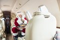 Santa with head in hands sleeping in private jet man costume Stock Images