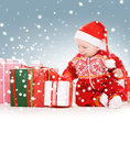 Santa helper baby with christmas gifts picture of Stock Photos